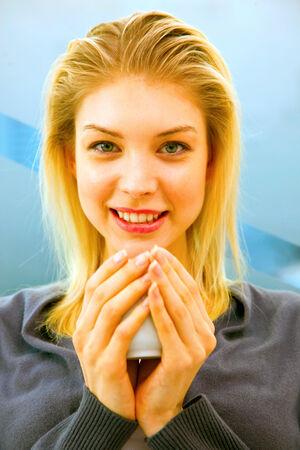 tomando refresco: Primer plano de la sonrisa joven mujer con taza