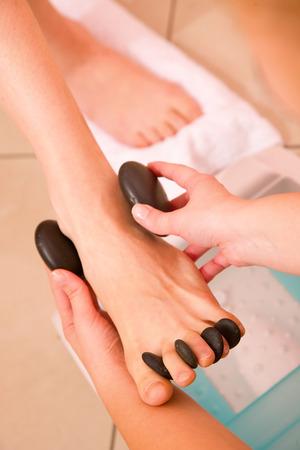 Mujer que recibe pies masaje con piedras calientes