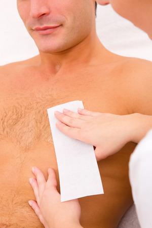 depilacion con cera: El hombre encerar su pelo en el pecho Foto de archivo