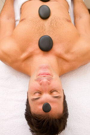 body concern: Young man receiving hot stone treatment