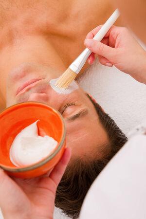 self indulgence: Therapist applying cream mans face Stock Photo