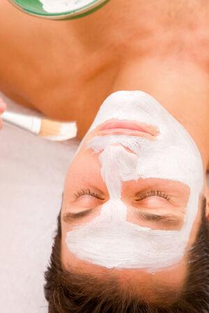 self indulgence: Young man having facial spa treatment