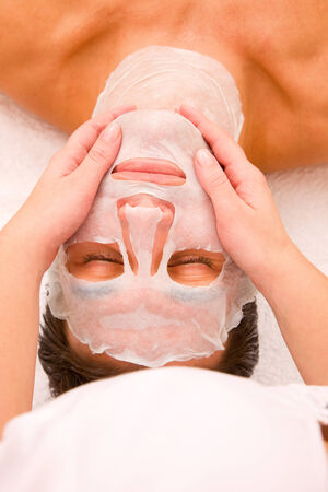 self indulgence: Therapist applying face mask mans face Stock Photo