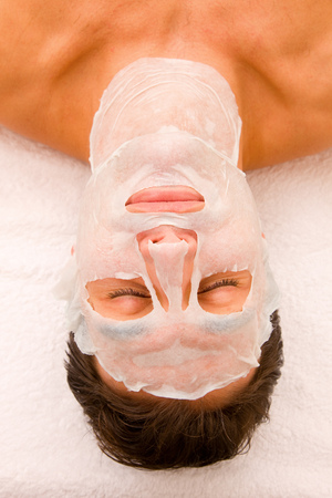 self indulgence: Close-up of a young man with face mask
