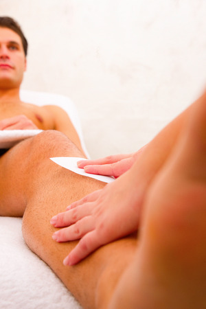 depilation: Man getting his leg waxed