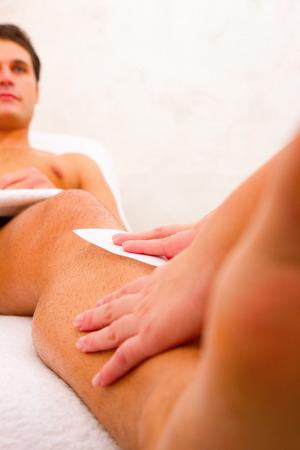 waxing: Man getting his leg waxed