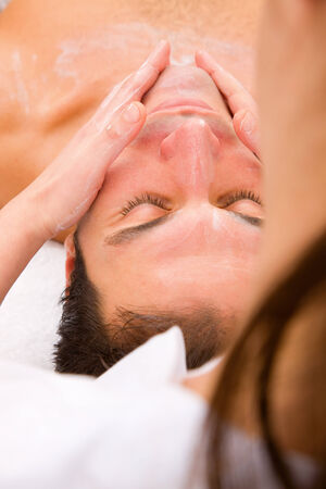 self indulgence: Beautician applying moisturizer mans face Stock Photo