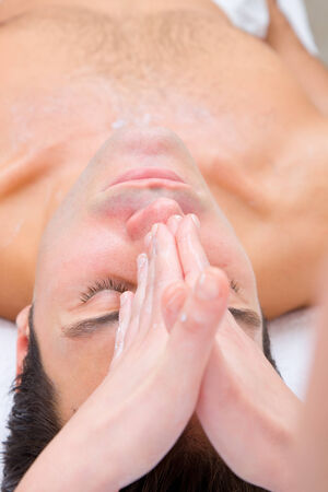 self indulgence: Young man getting a face massage from masseuse Stock Photo