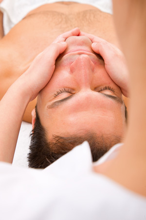 Close-up of young man getting face massage photo
