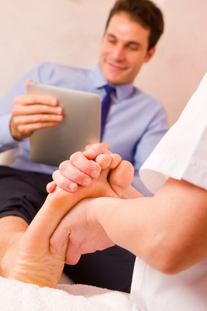 Masseuse massaging businessmans foot