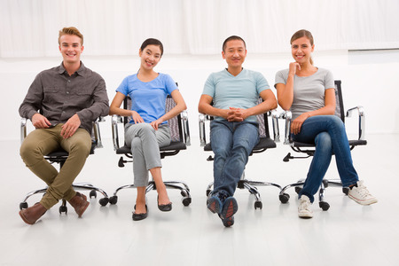 Multi ethnic group of people sitting office chair