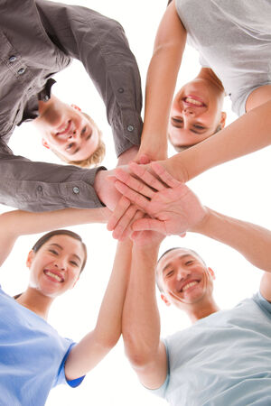 Happy businesspeople placing their hands top of each other photo