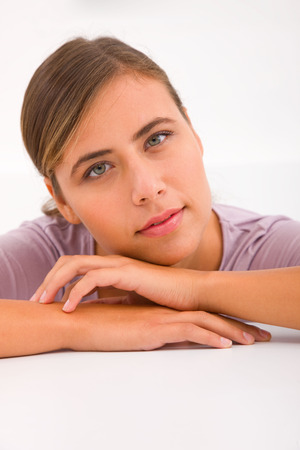 leaning forward: Young woman leaning forward desk Stock Photo