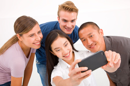 Happy multiethnic friends taking self portrait with cell\ phone