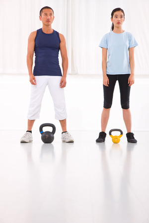 Asian man and woman doing kettle bell crossfit exercise photo