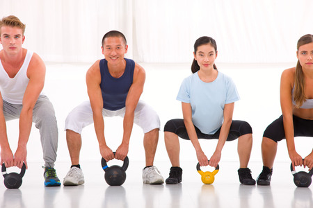 Multiethnic group of people doing kettlebell crossfit exercise photo