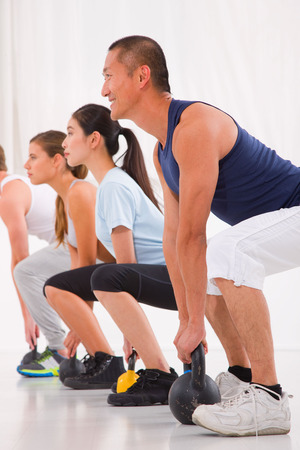 Diverse group practicing kettlebell exercise in crossfit gym photo