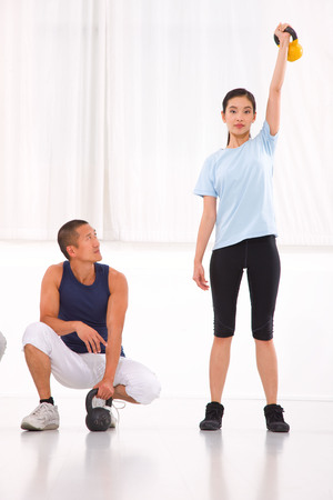 Asian man looking woman doing kettle bell crossfit exercise photo