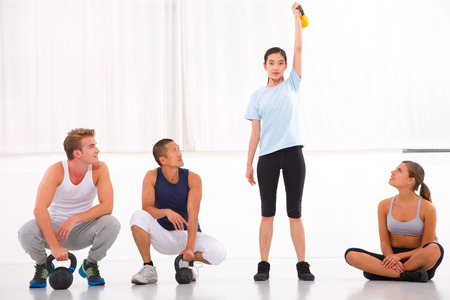 Group of diverse people looking woman lifting kettlebell in gym photo
