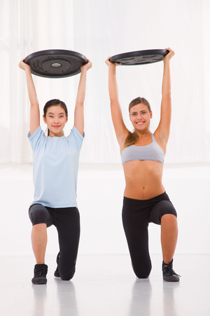 self improvement: Two young woman lifting weight in gym