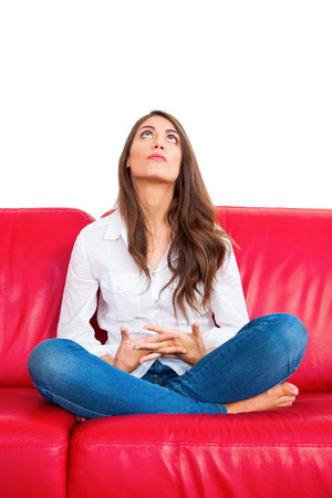only women: Full length of thoughtful young woman. Beautiful female with hands clasped is sitting on red sofa. She is isolated over white background.