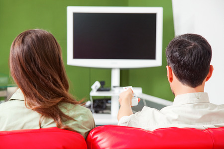 Rear view of young couple watching TV. Male and female partners are sitting on red sofa. They are at home. Stock Photo