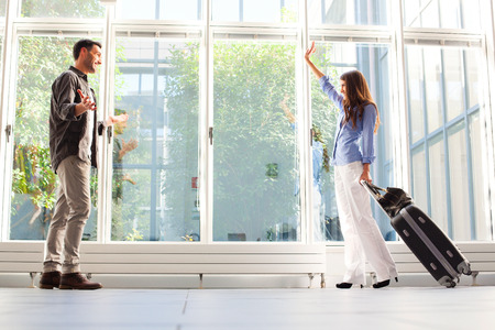 casuals: Full length of woman with luggage waving to her boyfriend. Young male and female partners are at airport. They are in casuals.