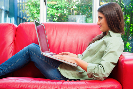 casuals: Side view of young woman using laptop. Smiling female is in casuals sitting on sofa. She is surfing the internet at home. Stock Photo