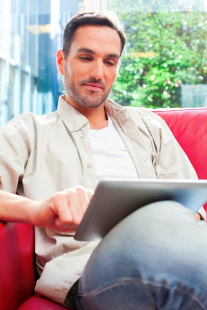 three people only: A photo of young man using digital tablet. Confident male is in casuals sitting on sofa. He is surfing the internet against window at home.