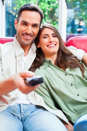 pareja viendo television: Retrato de joven pareja feliz viendo la televisión. Las parejas masculinas y femeninas están en el sofá. Están sentados en casa.