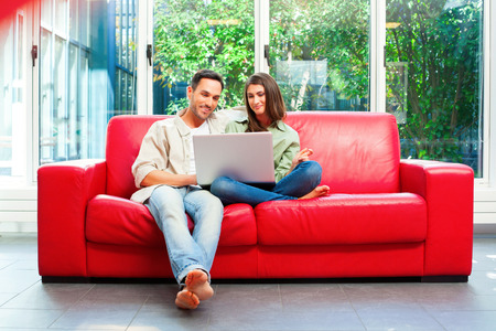 casuals: Full length of young couple using laptop. Happy male and female partners are sitting on red sofa. They are in casuals at home.