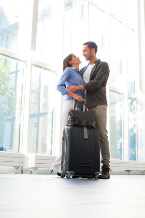 travel bag: Full length of young couple embracing at airport. Romantic male and female partners are with luggage. They are in casuals. Stock Photo
