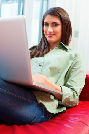 casuals: Portrait of young woman using laptop. Happy female is in casuals sitting on sofa. She is surfing the internet at home.