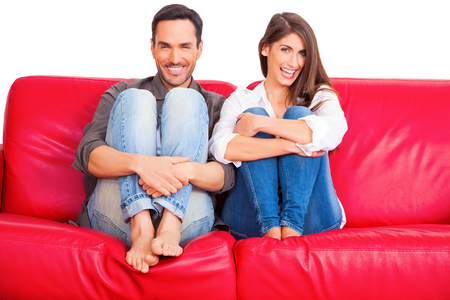 hugging knees: Full length of happy young couple relaxing on sofa. Loving male and female partners are in casuals. Both are hugging knees isolated on white background. Stock Photo