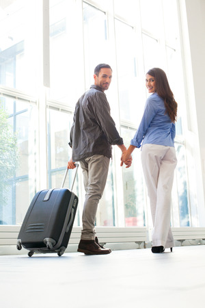 casuals: Full length of happy young couple with luggage at airport. Loving male and female partners are holding hands. They are in casuals. Stock Photo