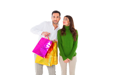 casuals: A photo of happy young woman looking at man carrying shopping bags. Male and female partners are in casuals. They are standing isolated over white background.