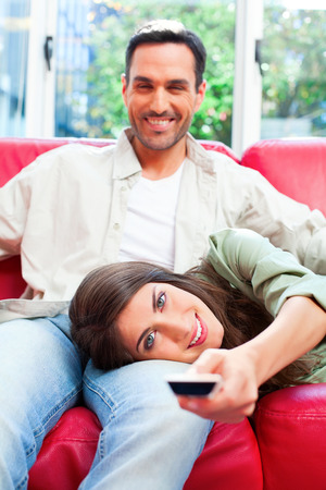 changing channels: Happy young woman lying on boyfriends lap while using remote control. Male and female partners are relaxing on sofa. Portrait of couple is at home.
