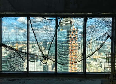 spacious view from the 42nd floor of the Skyliner Warsaw building, through the protective mesh on the window, towards the city center and the Buma building