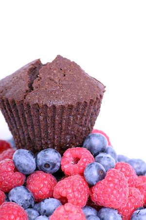 Delicious chocolate muffin on a white background with forest fruits photo