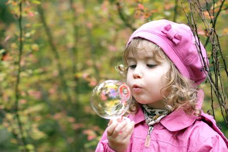 The charming and cheerful little girl lets soap bubbles