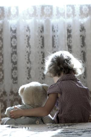 Depressed little girl hugging teddy bear photo