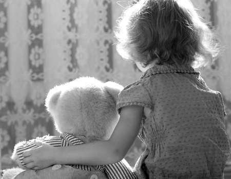 scared girl hugs a teddy bear