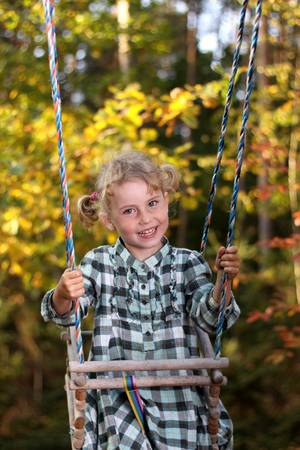 recollections: Little and pretty girl playing on a swing Stock Photo