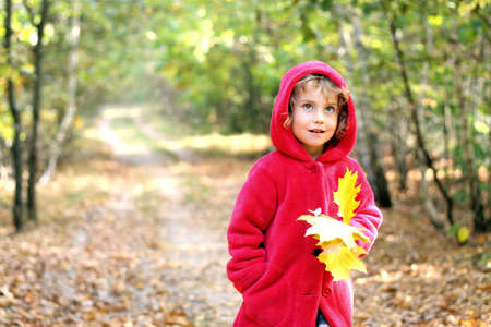 red scarf: The little girl in a red cap in the autumn forest