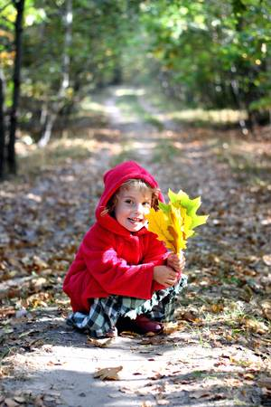 The little girl in a red cap in the autumn forest photo