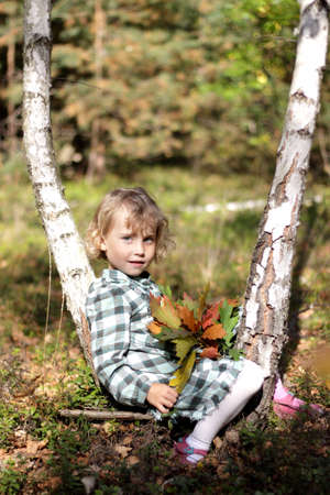 Little girl play outside in a sunny autumn day photo