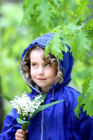 Lovely girl with a bouquet of lily of the valley photo