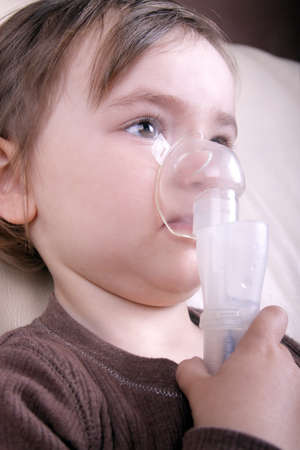 inhalation: A little girl uses a nebulizer for inhalation