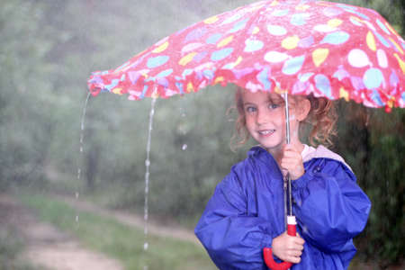 Young girl with an umbrella on a rainy day photo