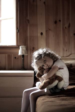 Depressed little girl hugging teddy bear